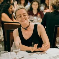 white person wearing a black tank top, choker, and glasses with partially shaved and blonde hair sits at a table. they are smiling, looking down to the left, and gesturing a push away to the left.