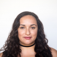 A headshot of a mixed-race (Colombian and Assyrian) woman with brown, shoulder-length wavy hair looking directly into the camera. She is wearing a black choker necklace.