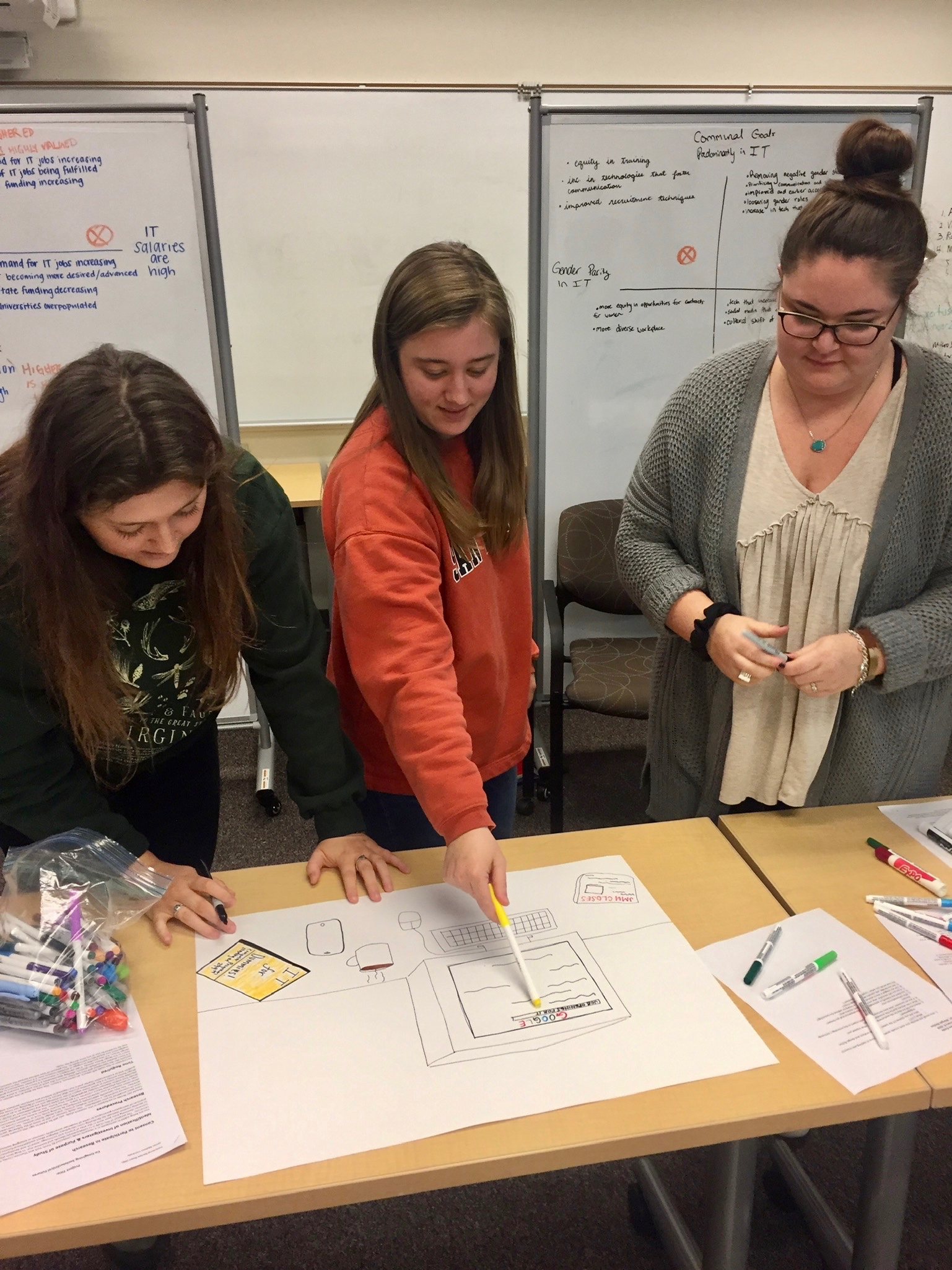 Three undergraduate student members of the STS Futures Lab collaborate on a design fiction prototype as part of the Co-Imagining Futures workshop
