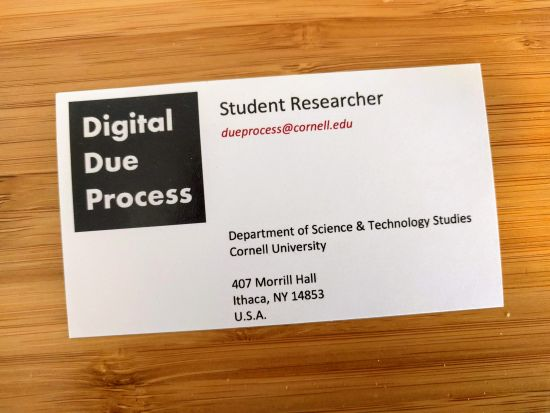 A photo of a business card for student researchers at the Digital Due Process Clinic, showing the clinic logo and contact data